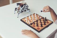 Un niño pequeño está jugando a ajedrez con un robot gris Juegos del robot para los blancos Fotografía de archivo libre de regalías