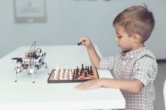 Un niño pequeño está jugando a ajedrez con un robot gris Juegos del robot para los blancos Imágenes de archivo libres de regalías