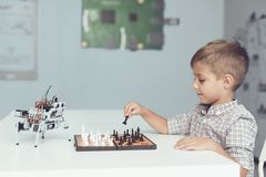 Un niño pequeño está jugando a ajedrez con un robot gris Juegos del robot para los blancos Foto de archivo libre de regalías