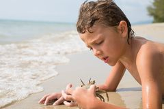 Un niño pequeño feliz que juega en la playa en el tiempo del día Fotografía de archivo