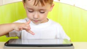 Un niño pequeño feliz que se sienta en una tabla toca la visualización electrónica de la tableta Un niño está jugando con un orde metrajes
