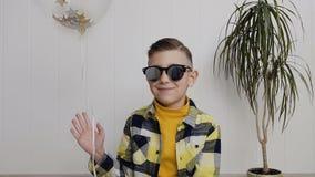 Un niño pequeño hermoso en gafas de sol se sienta en el piso contra la perspectiva de una pared blanca y sostiene un globo almacen de metraje de vídeo