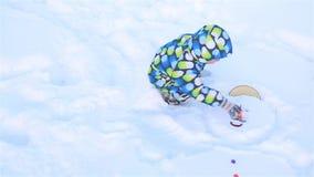 Un niño pequeño intenta sacar una nariz resbaladiza de un muñeco de nieve almacen de video