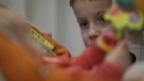 Un niño pequeño juega en un asiento infantil Cerrar con las manos del bebé El hermano mayor vigila las acciones de la hermana metrajes