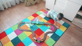 Un niño pequeño juega en el tren, corriendo después de él para alcanzar almacen de metraje de vídeo