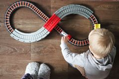 Un niño pequeño juega un ferrocarril de los niños La mamá está mirando a su hijo desde arriba El tren fascina al niño imagenes de archivo