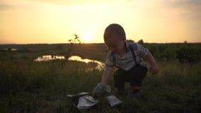 Un niño pequeño lanza feliz una pila enorme de billetes de dólar al aire libre en la cámara lenta almacen de metraje de vídeo