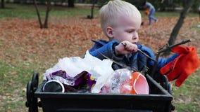 Un niño pequeño lanza la basura en la basura en la calle El concepto de gestión de desechos y de protección del medio ambiente Ap metrajes