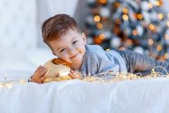 Un niño pequeño lindo con una bola del juguete de los christmass delante del árbol de navidad en la cama amor, concepto de la fel imágenes de archivo libres de regalías