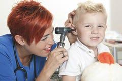 Un niño pequeño lindo del doctor Examining imagen de archivo libre de regalías