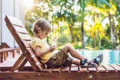Un niño pequeño lindo está utilizando un smartphone que miente en un deckchair cerca Fotos de archivo libres de regalías