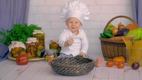 Un niño pequeño lindo juega en la cocina con las verduras frescas