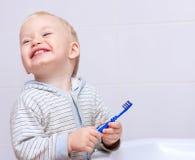 Un niño pequeño lindo limpia sus dientes Imágenes de archivo libres de regalías