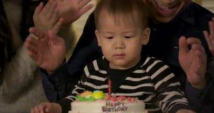 Un niño pequeño lindo que se sienta en la tabla y las velas que soplan en la torta de cumpleaños en la cámara lenta almacen de video