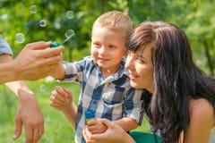 Un niño pequeño mira en burbujas de un jabón El papá lleva a cabo su mano a del ` s del hijo Fotografía de archivo libre de regalías