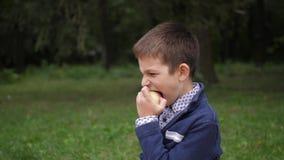 Un niño pequeño muerde una manzana y sonrisas Cámara lenta 4K metrajes