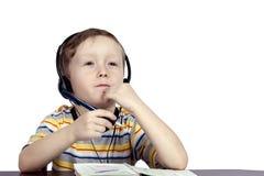 Un niño pequeño piensa los auriculares con el micrófono Imagen de archivo