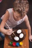 Un niño pequeño pinta los huevos la víspera de Pascua, de las pinturas coloridas y de cepillo, foto de archivo libre de regalías