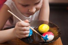 Un niño pequeño pinta los huevos la víspera de Pascua, de las pinturas coloridas y de cepillo, imagenes de archivo