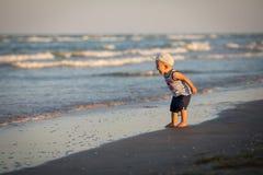 Un niño pequeño que descansa sobre el mar Imagen de archivo libre de regalías