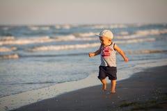 Un niño pequeño que descansa sobre el mar Fotografía de archivo