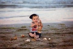 Un niño pequeño que descansa sobre el mar Foto de archivo