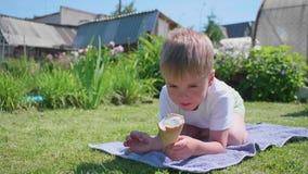 Un niño pequeño que miente en el césped y feliz de comer el helado Día de verano caliente, postre dulce frío almacen de metraje de vídeo