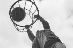 Un niño pequeño que salta y que hace la meta que juega el streetball, baloncesto Lanza una bola del baloncesto en el anillo El co Fotografía de archivo libre de regalías