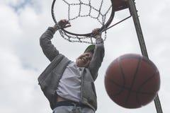 Un niño pequeño que salta y que hace la meta que juega el streetball, baloncesto Lanza una bola del baloncesto en el anillo El co Imágenes de archivo libres de regalías