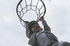 Un niño pequeño que salta y que hace la meta que juega el streetball, baloncesto Lanza una bola del baloncesto en el anillo El co Fotografía de archivo