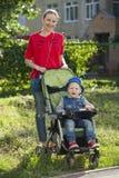 Un niño pequeño que se sienta en una silla de ruedas y que camina con su madre fotografía de archivo libre de regalías