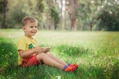 Un niño pequeño se está sentando con el teléfono en la hierba Imagen de archivo