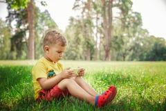 Un niño pequeño se está sentando con el teléfono en la hierba Foto de archivo