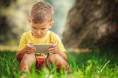 Un niño pequeño se está sentando con el teléfono en la hierba Fotografía de archivo libre de regalías