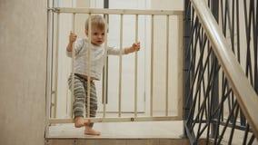Un niño pequeño se está sentando en casa delante de las escaleras detrás de las barras que no lo permitirán en otra parte de metrajes