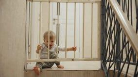 Un niño pequeño se está sentando en casa delante de las escaleras detrás de las barras que no lo permitirán en otra parte de almacen de metraje de vídeo