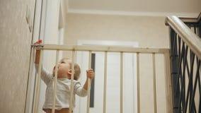 Un niño pequeño se está sentando en casa delante de las escaleras detrás de las barras que no lo permitirán en otra parte de almacen de video
