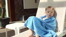 Un niño pequeño se está sentando en un ocioso del sol por la piscina envolvió en una toalla almacen de video