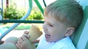 Un niño pequeño se está sentando en un oscilación en el parque y come el helado con placer Día de verano caliente, postre dulce f metrajes