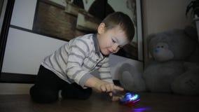 Un niño pequeño se sienta en el piso y los juegos con los juguetes almacen de metraje de vídeo
