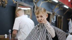 Un niño pequeño se sienta en una silla en una mirada de la barbería en la cámara y muestra con su mano que todo sea aceptable y é metrajes