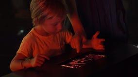 Un niño pequeño utiliza una PC de la tableta con un mapa astronómico del zodiaco Concepto de la educación de los niños almacen de video