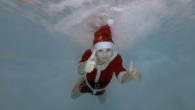 Un niño pequeño vestido como Santa Claus nada bajo el agua en los chorros de agua en la piscina con sus ojos abiertos, sonrisas,