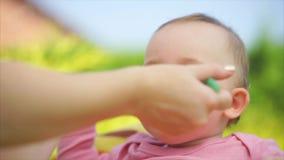 Un niño pequeño y divertido come las gachas de avena de mi cuchara del ` s de la madre en el aire abierto almacen de video