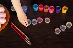 Un niño pinta los huevos de Pascua mano, brocha y pintura en la tabla Preparación para Pascua fotos de archivo