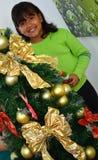Un niño que adorna un árbol de navidad con las chucherías Foto de archivo
