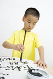Un niño que escribe caligrafía china Imagen de archivo libre de regalías