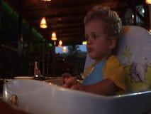 Un niño que espera ansiosamente su cena en un restaurante almacen de video