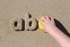 Un niño que hace letras de la arena en la playa Fotos de archivo libres de regalías