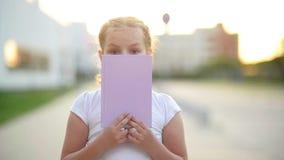 Un niño que juega con un libro Ella se está divirtiendo mucho La voluntad del libro da a su mucho conocimiento Ella mira almacen de metraje de vídeo